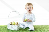 Fotografie cute child holding yellow chicken egg while sitting near straw basket with Easter eggs isolated on white