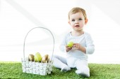 adorable kid holding yellow chicken egg while sitting on green grass near straw basket with Easter eggs isolated on white