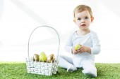 cute blonde baby holding yellow chicken egg while sitting near straw basket with Easter eggs  isolated on white