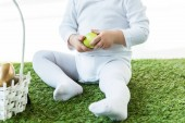 Fotografie partial view of baby sitting on green grass and holding yellow chicken egg isolated on white