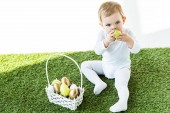 Fotografie cute child holding yellow kitchen egg near face while sitting near straw basket with Easter eggs isolated on white