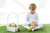 adorable child sitting near straw basket with colorful Easter eggs isolated on white