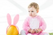 cute kid in pink fluffy costume holding colorful quail eggs while sitting near yellow ostrich egg with bunny ears headband isolated on white