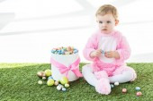 Fotografie adorable baby in pink fluffy costume sitting on green grass near box with colorful Easter eggs isolated on white