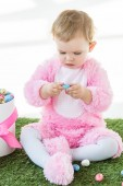 cute kid in pink fluffy costume holding blue quail egg while sitting near box with Easter eggs isolated on white