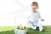 Fotografie adorable child sitting on green grass near straw basket with yellow and golden Easter eggs isolated on white