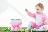 adorable child in pink fluffy costume holding quail egg in outstretched hand while sitting near box with colorful Easter eggs isolated on white