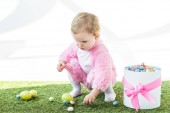 Fotografie adorable kid in pink fluffy costume taking colorful eggs from green grass near gift box with pink bow isolated on white