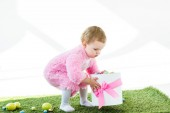 Fotografie adorable kid in pink fluffy costume holding gift box with pink bow and colorful Easter eggs isolated on white