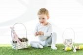 cheerful baby sitting near straw baskets with Easter eggs, decorative rabbits and happy Easter card isolated on white
