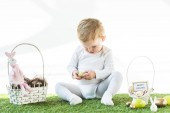 Fotografie adorable child sitting near straw baskets with Easter eggs, decorative rabbits and happy Easter card isolated on white