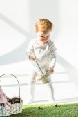 adorable child holding straw basket while standing on green grass in sunlight