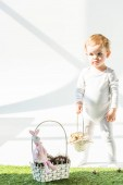 cute baby holding straw basket while standing on green grass in sunlight