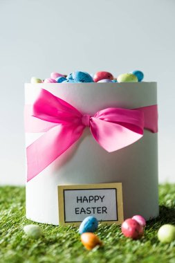 gift box with pink bow full of colorful quail eggs isolated on grey