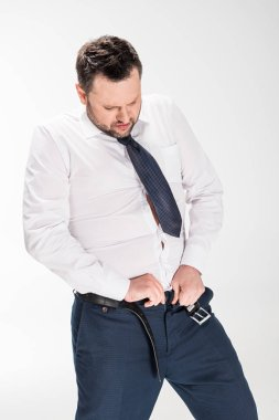 Overweight man in formal wear putting on tight pants on white stock vector