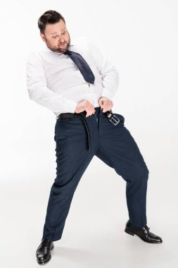 overweight man in formal wear putting on tight pants on white