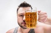 Photo overweight man looking at camera and covering face with glass of beer isolated on white