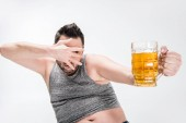 overweight man covering face with hand and holding glass of beer isolated on white