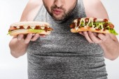 partial view of overweight man holding delicious hot dogs isolated on white