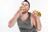 overweight man in tank top eating tasty hot dog isolated on white