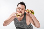 Fotografie overweight man in tank top eating tasty hot dog isolated on white