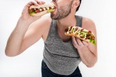 cropped view of overweight man eating hot dog isolated on white
