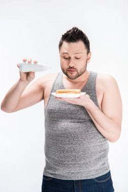 overweight man holding bottle of syrup and waffles isolated on white