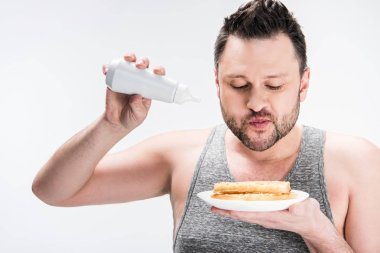 chubby man holding bottle of syrup and waffles on white