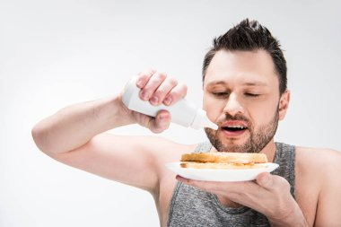 chubby man pouring chocolate syrup on waffles isolated on white