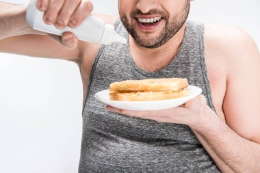 cropped view of overweight man holding bottle of syrup and waffles isolated on white