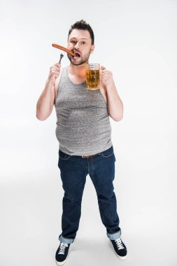 overweight man biting sausage and holding glass of beer on white