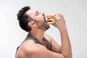side view of chubby bearded man eating delicious burger isolated on white