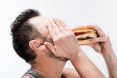 chubby bearded man covering face with hand while eating burger isolated on white