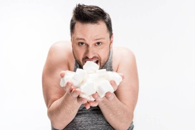overweight man holding marshmallows and looking at camera isolated on white