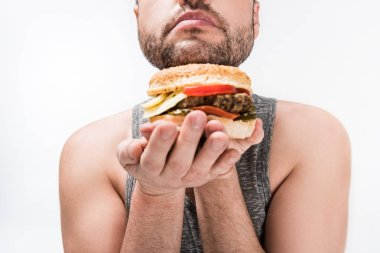 Cropped view of overweight man holding delicious burger isolated on white stock vector
