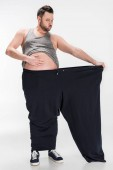 Photo overweight man touching belly while holding oversize pants after weight loss on white