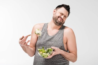 Displeased overweight man holding bowl of salad and making face expression isolated on white stock vector