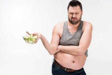 overweight man holding bowl of salad in disgust isolated on white