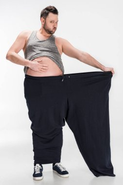 overweight man touching belly while holding oversize pants after weight loss on white