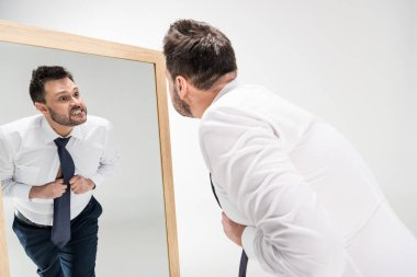 Angry overweight man in formal wear looking at reflection in mirror on white stock vector