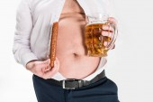 partial view of overweight man showing belly and holding glass of beer with grilled sausage isolated on white