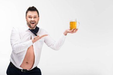 happy overweight man in tight shirt holding glass of beer and gesturing with hand isolated on white with copy space