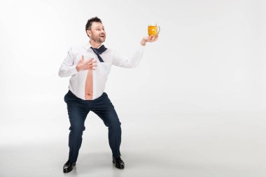smiling overweight man in tight shirt holding glass of beer and gesturing with hand on white with copy space