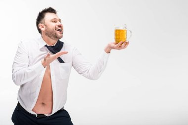 smiling overweight man in tight shirt holding glass of beer and gesturing with hand isolated on white