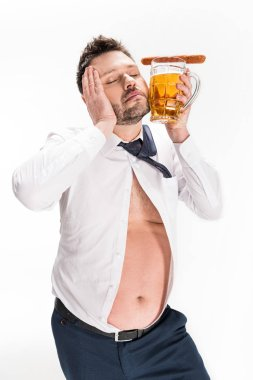 overweight man holding glass of beer with sausage and posing with eyes closed isolated on white