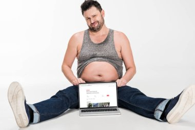 skeptical overweight man making facial expression and sitting with laptop with airbnb website on screen isolated on white