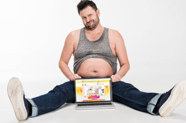 skeptical overweight man making facial expression and sitting with laptop with aliexpress website on screen isolated on white