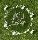 Fotografie top view of decorative bunnies scattered on green grass with happy Easter lettering in circle