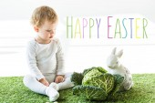 child sitting near savoy cabbage and decorative rabbit on green grass with happy Easter lettering