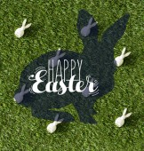 Fotografie top view of decorative bunnies on green grass with happy Easter lettering